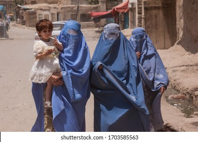 Kabul, Afghanistan - May 2004: Women in burqas in Kabul walking with a child