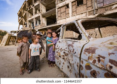 Kabul, Afghanistan September 2004: Children play around bullet-riddled car in Kabul