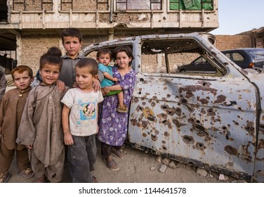 Kabul, Afghanistan September 2004: Children play around bullet-riddled car in Kabul