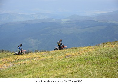 Kabul, Rila Mountain, Bulgaria - June 9, 2019: Two young men off-road motor-bikers riding endure motorcycles high on the slopes of Kabul Peak