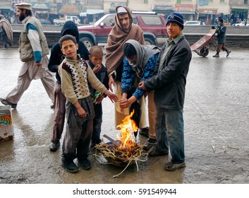 KABUL,AFGHANISTAN/MARCH 3, 2009: The children warm themselves by the fire in the street