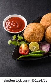 Kachori is a spicy snack from India also spelled as kachauri and kachodi. Served with tomato ketchup. Selective focus