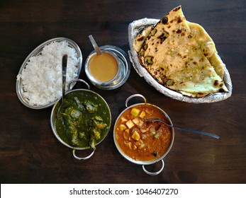 Kadai panner, chicken sagwala, garlic naan, masala tea and plain rice,  overhead view
