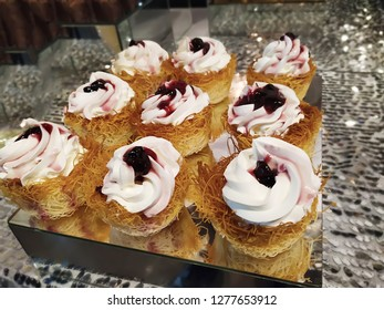 Kadaif Cupcakes with whipped cream and berries. Festive gourmet dessert