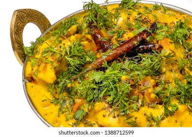 Kadhi Pakoda or pakora, Indian cuisine, served in a brass kadai or bowl isolated on white background.