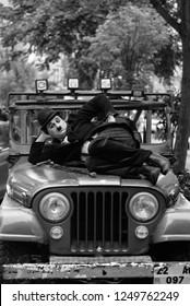 "Kadikoy, Istanbul / Turkey - April 6 2018: ""Charlie Chaplin"" performancer is lying on the vintage car (Black & White)"