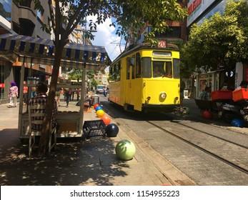 Kadikoy, Istanbul, Turkey - August 8, 2018: Nostalgic tramway and street food seller in Bahariye Street.