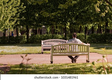 The Kadriorg park is the living room of the people living in Tallinn, the capital of Estonia. This man is excercising sitting on a park bench on a sunny summer day.