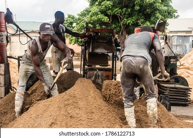 Kaduna, Nigeria - July 29 2020: African laborers shoveling sand and working with building materials.