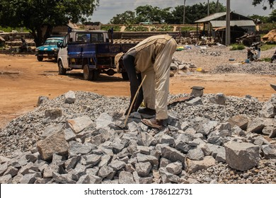Kaduna, Nigeria - July 29 2020: African laborer in dirty clothes breaking rocks with a hammer on a sunny day.