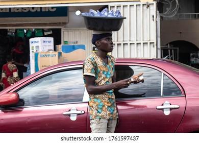 Kaduna, Nigeria - June 11 2020: Boy selling pure water. An African boy selling pure water on the road beside a red car,