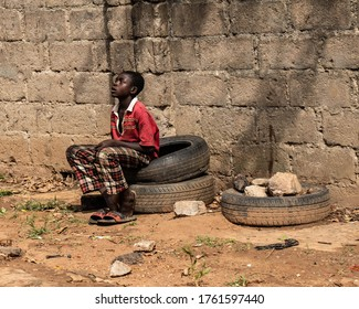 Kaduna, Nigeria - June 11 2020: African child. An African child in dirty clothes, sitting on some tyres.