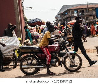 Kaduna, Nigeria - June 11 2020: Young boy riding a motorcycle. This picture shows a young african boy riding a motorcycle along a market scene.