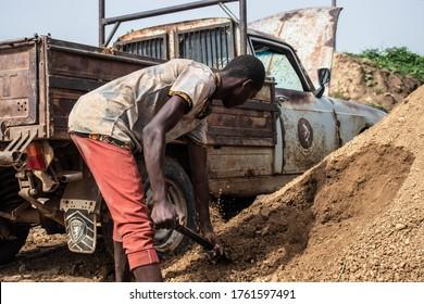 Kaduna, Nigeria - June 11 2020: Young African boy shovelling sand. An African boy shovelling sand into the back of a truck.
