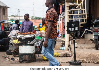 Kaduna, Nigeria - June 11 2020: A local market scene. This picture features a man walking past a 'no parking' sign in front of a man selling  roasted chicken.