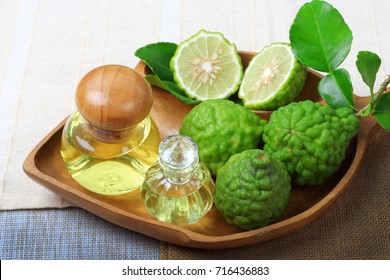 Kaffir lime or bergamot with aromatic spa of bottles essential oil on sack background.