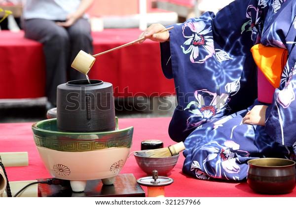 KAGAWA, JAPAN - SEPTEMBER 23, 2015: Japanese woman in traditional kimono prepares the tea ceremony at garden of the Hagiwara Temple on September 23, 2015 in Kagawa Japan.