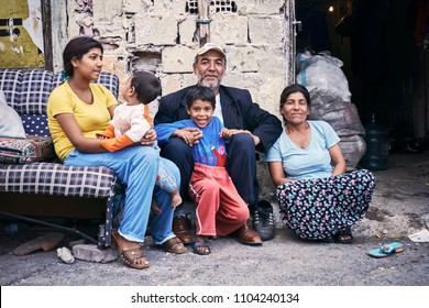 KAGITHANE GULTEPE, ISTANBUL, TURKEY - AUG. 2008: Family portrait of a poor Turkish romani people sitting on the street in front of their shanty house. Editorial use only.