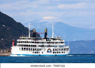 KAGOSHIMA CITY, JAPAN - FEBRUARY 15: Sakurajima Ferry crossing Kinko Bay, February 15, 2011. In the background is  Kirishima Mountain range where Mt Shinmoedake volcano began erupting in early 2011