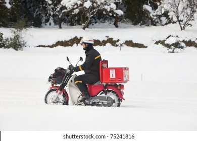KAGOSHIMA CITY, JAPAN - JANUARY 1: Japan Post employee on a motorcycle delivers mail after a very rare heavy snowstorm which crippled the city for days. Kagoshima City, Japan, January 1, 2011.