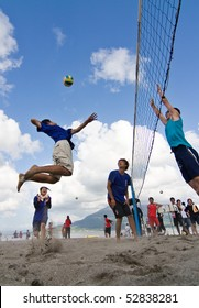 KAGOSHIMA CITY, JAPAN - JULY 6: A male volleyball player jumps to spike at the Iso Beach Volleyball Competition July 6, 2007  in Kagoshima City, Japan.