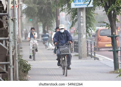 KAGOSHIMA CITY, JAPAN - JUNE 3: Cyclists cover their faces to protect from ash which blanketed the city after an  eruption of the  volcano Sakurajima   June 3, 2010 in Kagoshima City, Japan.