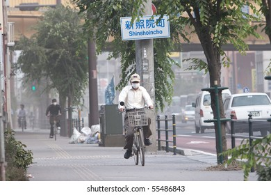 KAGOSHIMA CITY, JAPAN - JUNE 3: Cyclists cover their faces with masks to protect from ash which blanketed the city after an eruption of the volcano Sakurajima June 3, 2010 in Kagoshima City, Japan.