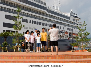 KAGOSHIMA CITY, JAPAN -OCTOBER 8: A family poses in front of the first cruise ship to dock at the newly built marine port, the ms Amsterdam October 8, 2007 in Kagoshima City, Japan
