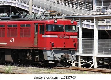 KAGOSHIMA, JAPAN - APRIL 10, 2010: JR freight train with ED761012 locomotive passing Kagoshima Central Station (Kagoshima Chuo Eki)