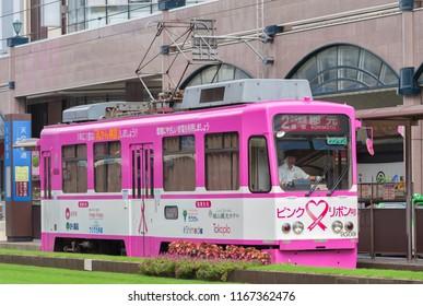 KAGOSHIMA, JAPAN - AUGUST 28, 2010: Kagoshima City Tram decorated with blue ribbon at station Tenmonkan-dori where the heart of Kagoshima city lies in