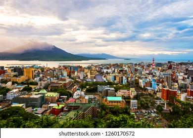 Kagoshima, Japan. View of mountain Sakurajima an active volcano. Aerial view of Kagoshima city in Japan at sunrise. Volcano eruption in the morning