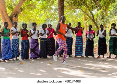 Kaguit vil., SENEGAL - APR 30, 2017: Unidentified Diola man in orange shirt and colored pants moves in front of women during a traditional dance Kumpo in a Sacred Forest near Kaguit village