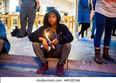 Kahari A. keeps a candle lit in homage of the shooting victims at the Don't Shoot Portland protest. Portland. Portland, OR, 7-7-2016.