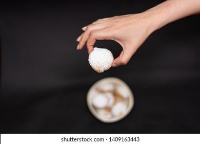Kahk cookies served on a brown plate, sprinkled with sugar and a female hand holding a cookie (Kahk is a traditional cookies in the arab world, served in Eid el fitr, a feast after Ramadan)
