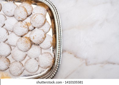 Kahk cookies served on a silver big plate sprinkled with sugar on top (Kahk is a traditional cookies in the arab world, served in Eid el fitr, a feast after Ramadan)  on a white marble background