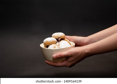 Kahk cookies served on a white plate, sprinkled with sugar and a female hand holding the plate (Kahk is a traditional cookies in the arab world, served in Eid el fitr, a feast after Ramadan)