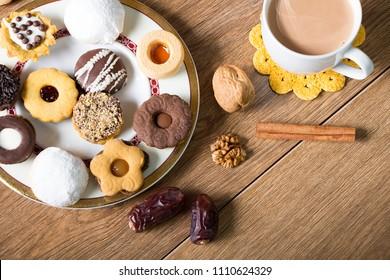 Kahk El Eid -  Kahk and cookies of Eid El Fitr Islamic Feast with cup of tea and milk