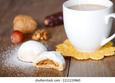 Kahk El Eid -  Cookies of Eid El Fitr Islamic Feast with nuts , hot tea and milk on wooden table
