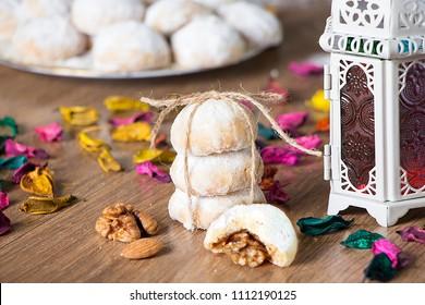 Kahk El Eid -  Homemade cookies of Eid El Fitr Islamic Feast decorated with rope ,dried flowers and Arabian lantern on wooden background