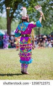 Kahnawake, Quebec, Canada - July 09, 2017 : Pow wow women's Jingle dancer at Kahnawake 27th Annual Echoes Of A Proud Nation Pow Wow in Kahnawake reserve. Juniors 12-17 years old category.