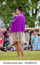 Kahnawake, Quebec, Canada - July 10, 2016 : PYoung mother with baby taking part in Kahnawake 26th Annual Echoes Of A Proud Nation Pow Wow in Kahnawake reserve