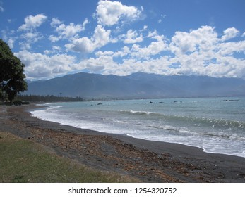 Kaikoura beach and mountains in the background with a cloude blue sky