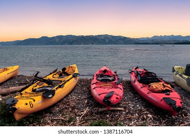 Kaikoura, New Zealand – 5 January 2019: lineup of colorful pedal kayaks on the pacific coast near Kaikoura at sunset