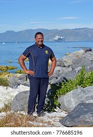 Kaikoura, New Zealand - December 15, 2017: Smiling Whale Watch Kaikoura Staff Member at South Bay Harbour with Cruise Liner in the background.