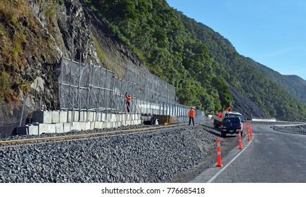 Kaikoura, New Zealand - December 15, 2017; Workmen rush to complete a  roadside falling rocks barrier prior to today's opening of State Highway One.