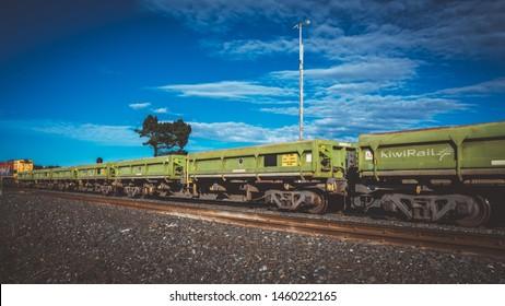 Kaikoura, New Zealand - May 9, 2019: Cargo train with bogie Hopper Wagon on blue sky background