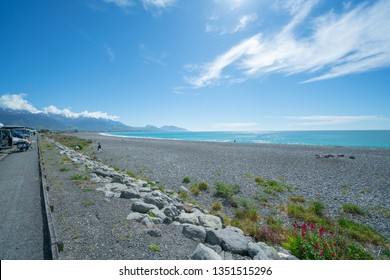 KAIKOURA NEW ZEALAND - OCTOBER 28; Stony Kaikoura beach and sea under blue sky with white cirrus clouds with people on beach and sitting at edge October 28 2018 Kaikoura New Zealand