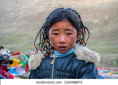 Kailash area, Tibet / China - Aug 2017: The tibetan young girl crossing the high altitude mountain pass during the ritual kora (yatra) around sacred Mount Kailash. Ngari scenery in West Tibet.