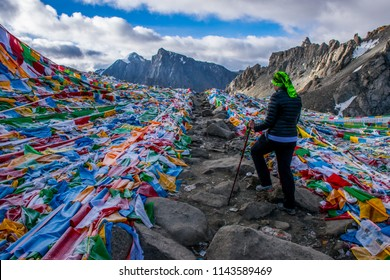 Kailash area, Tibet / China - Aug 2017: The european girl crossing the high altitude mountain pass during the ritual kora (yatra) around sacred Mount Kailash. Ngari scenery in West Tibet.