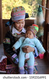 Kaili, China - October 29, 2019: At Hundreds of Birds Miao Village, portrait of a girl with her baby, wearing typical clothes and headgear of Miao minority